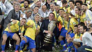Bolsonaro vai a campo, tira foto com taça e ouve 'mito' de jogadores